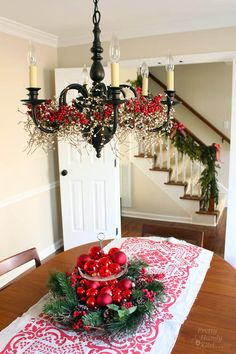 Add garland around the base of a chandelier for quick and pretty Christmas decorating. -Momo