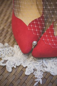 Charleston, SC Wedding | Beautiful red wedding shoes with a vintage birdcage veil, engagement ring and lace garter | Wedding photography by Charleston husband & wife wedding photographers @billiejojeremy. | Wedding Planner: @trustpinnacle      #birdcage #veil #redheels #vintage #garter #charlestonwedding #weddingdetails #engagementring #bride #charlestonphotographers #diamondearrings