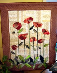 Appliqued poppies on a strip pieced background and quilted with free style flowers.