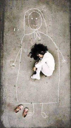 This photo was taken in an orphanage in Iraq. The little girl has never seen her mother, so she drew this figure on the ground and fell asleep with her...
