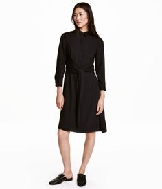 Black. Knee-length dress in soft woven fabric with a slight sheen. Collar…