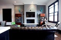 Living room in Daniel Lowe's Hollywood loft with tufted leather couch and trellis fretwork gray wallpaper on on the fireplace