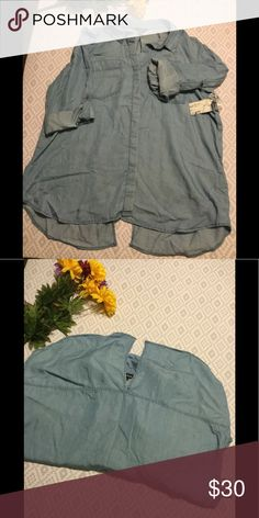 Terre Bleue Chambray Shirt This loose fit, rolled sleeve with tabs shirt has a high/low hem. Slit in the back hem gives it a tuxedo vibe. Tops Button Down Shirts