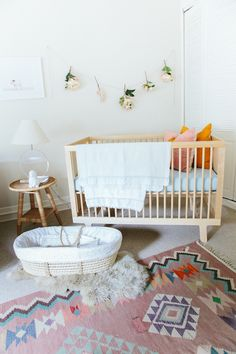 Adorable nursery features a modern wood crib and a woven moses basket atop a sheepskin layered over a pink kilim rug