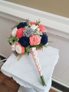 Wood flower bouquet in coral, Navy, gray and ivory. Cream satin wrapped handle with a soft coral criss cross ribbon. Contact The Bride & Bloom to order yours.
