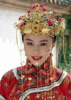 A red Chinese wedding gown topped by a gold phoenix crown