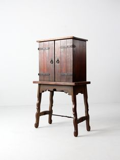 An antique Spanish Colonial style secretary desk circa early 20th century. The desk on frame features a secretary cabinet top with a fold down desk top and multiple compartment interior. The wood desk