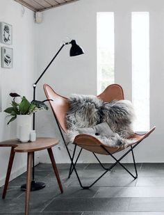 Reading corner with tan leather butterfly chair.