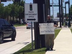 Outside the City of Humble photo enforcement office, Schirmbeck stood in protest and held a sign directed at drivers to never pay a camera light ticket.  Originally created in an effort to improve accountability and safety, the tickets are issued to the owner of the car and not to the driver, and drivers have expressed the inability to act quickly enough to slow down and stop to prevent passing a red light.  A year ago, Schirmbeck recorded a conversation with an Humble law enforcement…