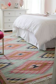 big rug under the bed to cover the carpet and bring color to the room