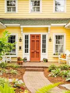 "With so much yellow siding, ""the house needed a door that would stand out,"" says Susie. She and Jerry liked this deep coral so much, they painted the storm door the same color."
