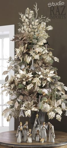 White Christmas Tree decorated with light Gold Silk Poinsettias!!! Bebe'!!! Love the nativity at the base of the tree!!!
