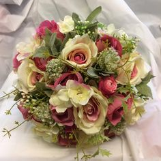a brides bouquet of roses, waxflower and ranunculas