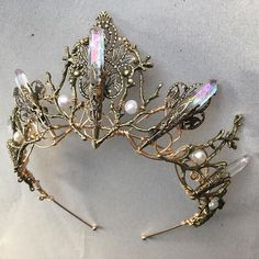 A magical hand made branch and filigree crown tiara, with angel aura quartz accents which shine rainbow colours as they catch the light. Available in brass (as shown), silver or gold, this crown is comfortable to wear, lightweight, and totally unique. Need another coloured crystal? No
