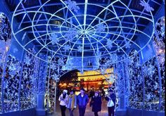 People walk in a corridor of lights built in front of a department store in Zhengzhou, Central China's Henan province, Dec 10, 2011. As Christmas and the New Year's Day approached, various decorations have been built by shopping malls, hotels and so on to warm up for festival sales promotions.[Photo/Xinhua]