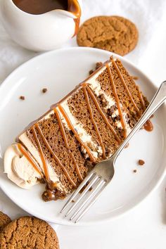 Slice of gingerbread cake on a plate with caramel drizzle over top.