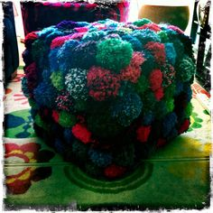 Pom Pom footstool. Got the idea from Pinterest and tried it myself. Up cycled an old fabric covered footstool, made Pom poms and sewed them onto the cover.