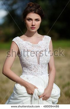 Portrait Of Young Beautiful Brunette Bride In White  Dress Outdoors. Professional Make Up and Hairstyle. Perfect face.
