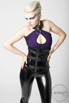 A PVC corset do we need to say more.... The front busk is covered but a flap of PVC that zips up to one side 3 Industrial clips cover the zipped up PVC Laces up. http://www.galleryserpentine.com/collections/corsets/products/vanta-black-pvc-corset