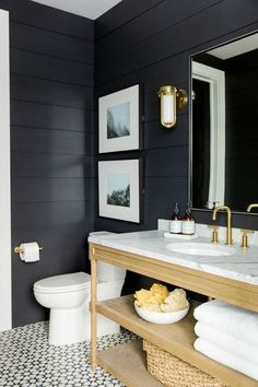 Modern Farmhouse combines traditional farmhouse elements with a fresh modern/industrial twist. Dark grey shiplap walls contrast with white sanitary fixtures and gold accessories
