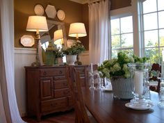 The design of the HGTV Dream Home 2004 dining room uses wainscoting to contrast boldly against the brown walls, while an antique mirror adds depth and personality to the space.