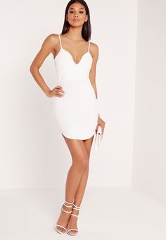 Plain dresses are easy to dress up or down - they scream out versatility. This white dress will be a hot addition to your wardrobe. Featuring a bodycon fit, daring plunge neckline and curved hem, this is an absolute beaut. Style with strapp...