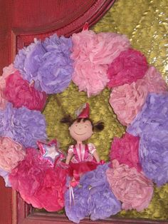 Princess or Pinkalicious birthday pom pom wreath.  Attached the poms to a straw wreath with floral pins.  Then added the Pinkalicious doll and wand.  Easy just takes a little time.