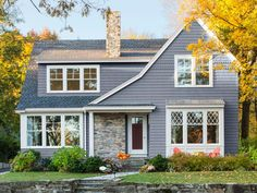 """Built in: 2011. SIze: 3,000 sq. ft. """"Since we built our home in a charming, architecturally diverse town, we didn't want it to look brand-new,"""" say homeowners Amy Cody and John Furst. """"Design choices like the sloped roofline and the stone facade and chimney give it a sense of history."""" The yard includes Endless Summer hydrangea, alpine Japanese spirea, and dwarf Hinoki cypress shrubs."""