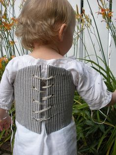 It sounds odd to us nowadays, but in the 18th century, babies and toddlers wore cardboard-stiffened stays (the 18th century take on a corset) to encourage a straight posture as soon as possible.  This one here is a modern-day replica made by the staff at Colonial Williamsburg in Virginia.  It does not look as restrictive as I thought it would be - note how the back isn't touching the child and how there is no cinching or narrowing at the waist.  According to the maker, it should feel like a…