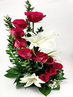 A ravishing twirl of red roses surrounded by white lilies.