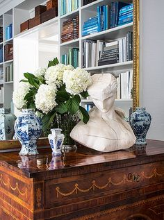 A substantial bust offsets ornate chinoiserie vases and intricate marquetrymotifs for a balanced effect.