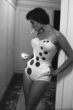 An international beauty queen models the latest swimwear. This piece includes circles on which to strike matches to light your cigarette on the beach. © John Sadovy