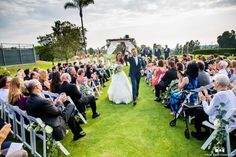 San Diego wedding at lomas santa fe country club bride strapless tulle ball gown with beaded bodice and purple sash with groom navy blue suit with matching vest and white dress shirt with white bow tie and white floral boutonniere walking down the aisle after ceremony