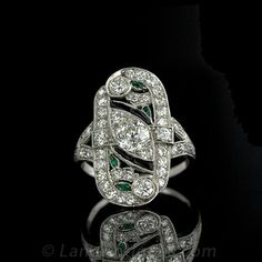 Love this original design: Chic original Art Deco dinner ring dazzling with diamonds, onyx and emeralds. This bold ring features 40 European cut diamonds set throughout the pierced mounting highlighted by calibre cut onyx and pear cut and marquise cut emeralds.