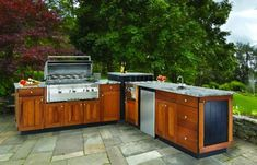 This patio kitchen has wooden cabinets and a granite countertop.