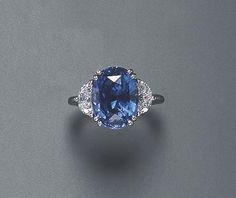 A SAPPHIRE AND DIAMOND RING Set with an oval-cut sapphire, weighing approximately 8.52 carats, flanked on either side by half moon-cut diamonds, mounted in platinum The total weight of the diamonds is approximately 1.10 carats