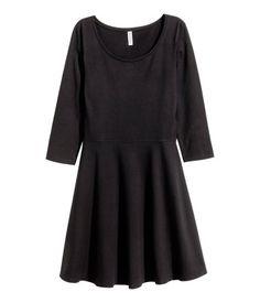 Een korte jurk van tricot met een iets wijdere halsopening, driekwart mouwen, een naad in de taille en een klokkende rok. Ongevoerd.