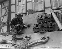 WWII, 1945 - Raymond Hurley of Hamilton, Ohio, First US Army, shows the hole made in the turret of a German Tiger II by a Bazooka.  The tank was knocked out in Osterode, Germany.
