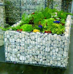Mit Gabionen kann man auch Hochbeete bauen. Die mit Steinen gefüllten Körbe verschönern zugleich den Garten.