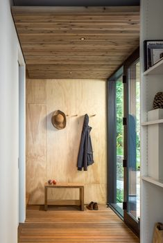 The use of plywood on the walls. Simple entry with ample hooks, place for bench and shoes, bright and open.