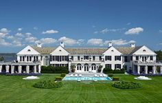 An all white South Hampton mansion with black shutters on a beautiful well-manicured lawn.