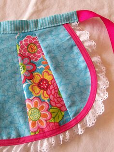 Patchwork half apron is made from 3 coordinating prints with the dominant color an aqua/blue. Bright, colorful flowers on some of the panels add color and the apron is edged in hot pink binding and white lace. Measurements: 11 wide at the waist, 14 wide at the widest part of the