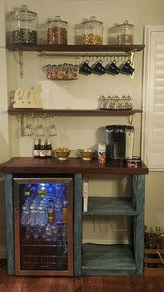 Custom coffee bar made by my husband. Top/shelves stained in mahogany -Bottom in wood stain old navy mixed with antique white for a white washed look. All gold accents spray painted metallic gold. Ikea wire baskets/hanging rod/wine glass rack/brackets.