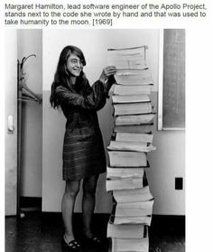 Margaret Hamilton, lead software engineer of the Apollo project, standing next to the code she hand wrote which was used to take humanity to the moon