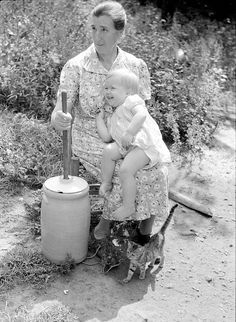 Woman churning butter with toddler in her lap.