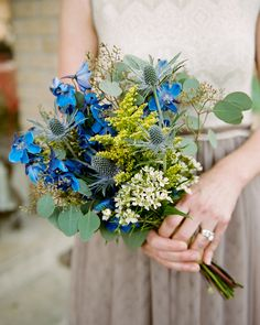 """The vivid blue are delphinium. The large flat leaves are seeded eucalyptus. The """"thistle"""" looks like Sea Holly (Eryngium)."""