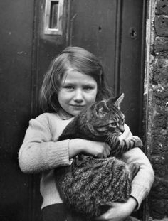 """""""Wartime Rationing"""" 1947 - 6-year-old girl (name unknown) holding her fat cat. Prior to World War Two, there were no pet foods: family pets shared their owner's foods, often eating the scraps off the plates. This continued throughout the war."""""""