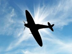 Silhouette of Vintage British World War 2 fighter plane in a blue sky. - Artists Impression.