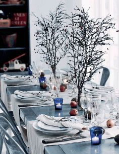 Holiday-decor-inspired-by-nature. Berry laden branches and apples strewn casually on the table with candlelight and lovely linens. The height of the branches adds a bit of drama to a low key table. Holiday or everyday. Make your table a joy to behold.