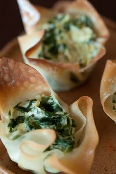 SPINACH & ARTICHOKE CUPS: Ingredients: 24 wonton wrappers 1 1/2 cup frozen spinach, thawed and chopped 1 1/2 cup artichoke hearts, chopped 6 oz cream cheese 1/4 cup sour cream 4 tbsp Parmesan cheese 1 tsp red pepper flakes salt and pepper to taste